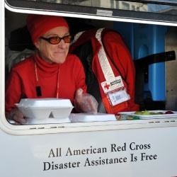 Woman in red cross van handing out food